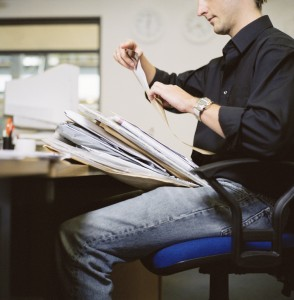 Man with Stack of Paperwork at the Office
